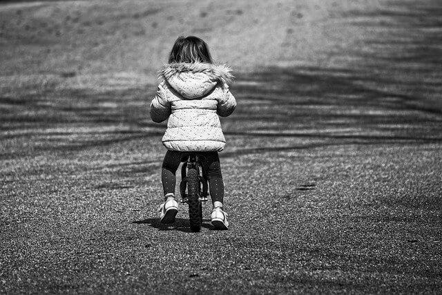 Une petit fille en équilibre sur une draisienne sur une route